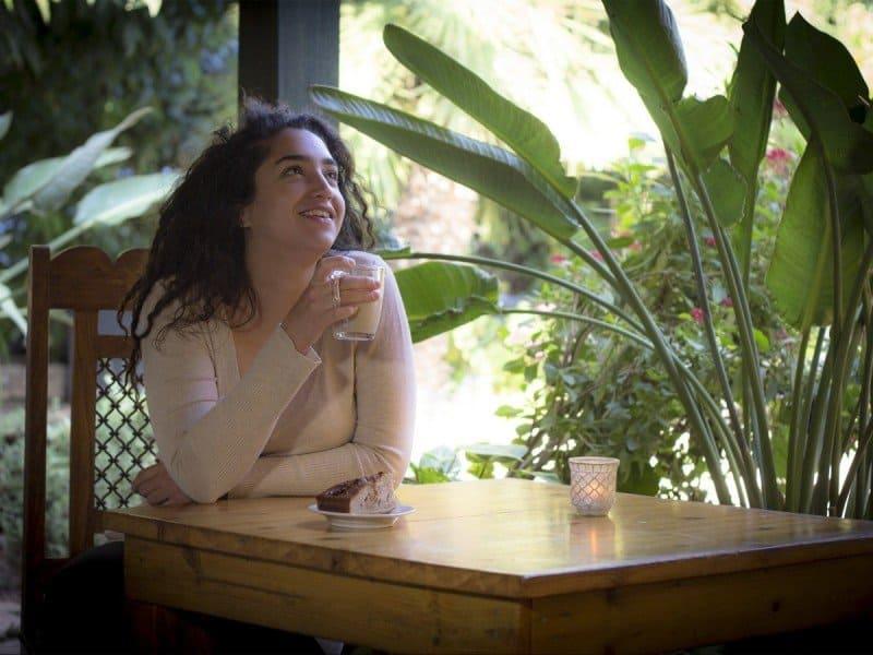 בחורה שותה קפה בשולחן