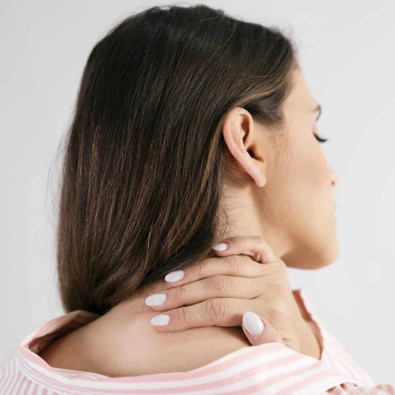Rear view of young woman suffering from neck pain
